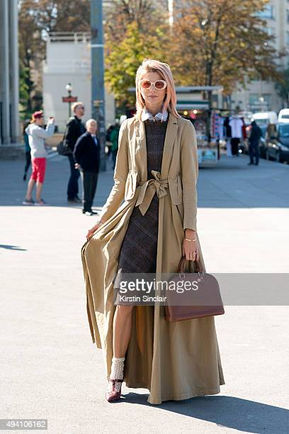 Fashion Blogger Samantha Angelo wears a Dries Van Noten coat Acne dress and sunglasses Louis Vuitton bag and Charlotte Olympia shoes on day 3 during...