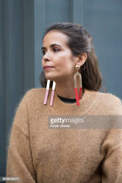 Fashion blogger Sara Escudero wears Topshop earrings And other stories sweater on day 2 of London Womens Fashion Week Spring/Summer 2018 on September...
