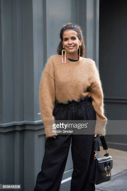 Fashion blogger Sara Escudero wears Topshop trousers and earrings JW Anderson bag and And other stories sweater on day 2 of London Womens Fashion...