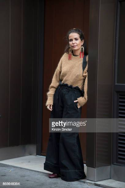 Fashion blogger Sara Escudero wears Topshop trousers and earrings JW Anderson bag Jonak boots and And other stories sweater on day 2 of London Womens...