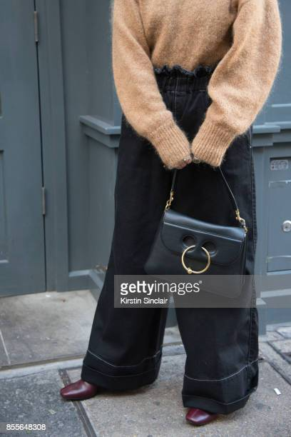 Fashion blogger Sara Escudero wears Topshop trousers JW Anderson bag Jonak boots and And other stories sweater on day 2 of London Womens Fashion Week...