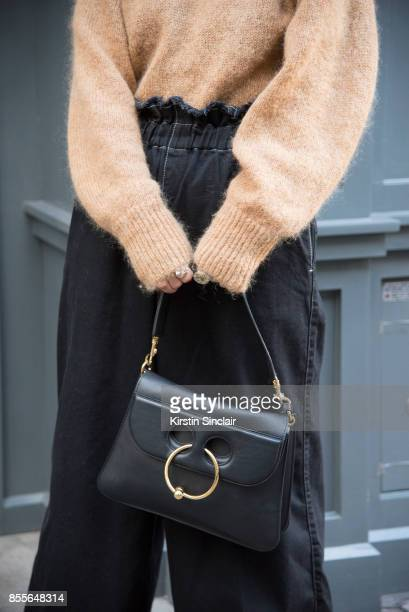 Fashion blogger Sara Escudero wears Topshop trousers JW Anderson bag and And other stories sweater on day 2 of London Womens Fashion Week...