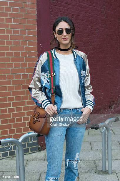 Fashion blogger Soraya Bakhtiar wears an ASOS bomber jacket Leviâs jeans IRO sweater Gucci bag and Ray Ban sunglasses on day 5 during London Fashion...