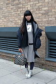 Fashion blogger Susie Lau wears a Reay coat JW Anderson dress Louis Vuitton bag and Dora Teymur boots on day 3 of London Collections Men on Januay 10...
