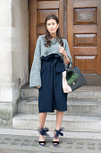 Fashion Blogger Sylvia Haghjoo wears a Phillip Lim sweater Fendi bag Tibi skirt Jimmy Choo shoes Dior earrings and Georg Jensen jewellery on day 3...