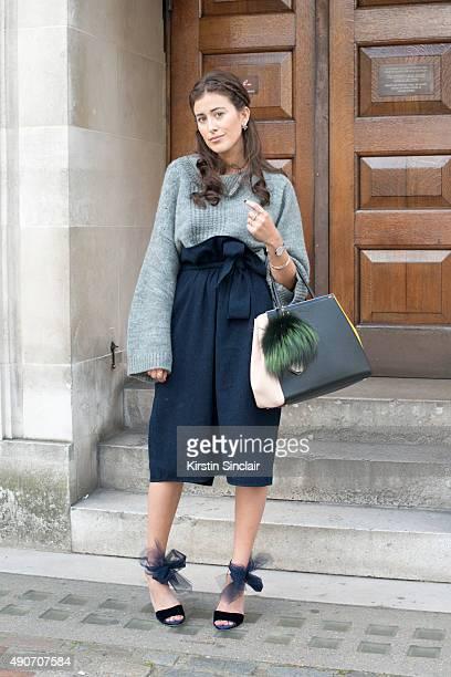 Fashion Blogger Sylvia Haghjoo wears a Phillip Lim sweater Fendi bag Tibi skirt Jimmy Choo shoes Dior earrings and Georg Jensen jewellery on day 3...