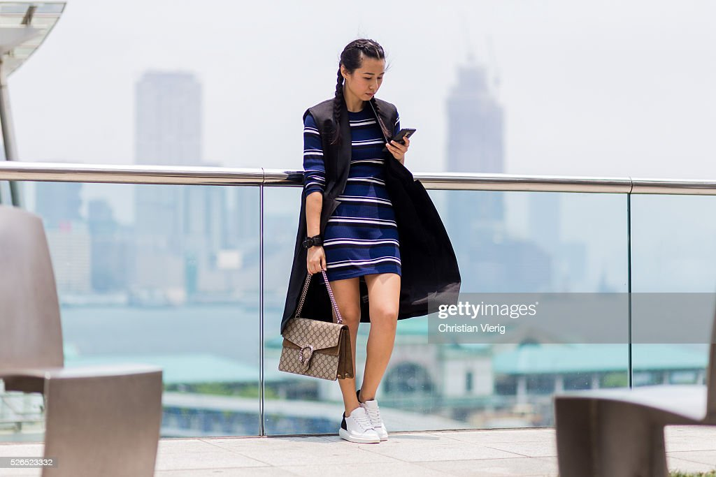 Fashion blogger Theresa Twee Wu with braids wearing a navy black white striped H&M dress, a Gucci Dionysus shoulder bag, a black C Meo Collective long vest and white Pedder Red sneakers on April 30, 2016 in Hong Kong, Hong Kong.