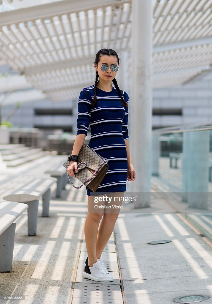 Fashion blogger Theresa Twee Wu with braids wearing a navy black white striped H&M dress, a Gucci Dionysus shoulder bag and white Pedder Red sneakers on April 30, 2016 in Hong Kong, Hong Kong.