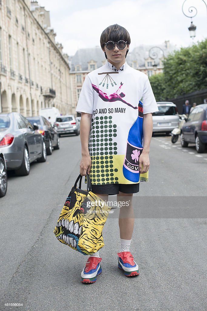 Fashion blogger Weichen Gao wearing a Raf Simons top and trainers, Jeremy Scott bag and sunglasses from a market in Korea on day 1 of Paris Collections: Men on June 25, 2014 in Paris, France.