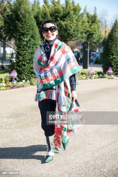 Fashion buyer and stylist Tera Feng wears an Angel Chen poncho boots and bag on day 3 during Paris Fashion Week Autumn/Winter 2017/18 on March 2 2017...