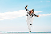 Happy little girl dance on sky background. Fashion kid. Copy space.