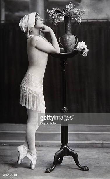 Fashion Circa early 1900's A lady leaning up against a tall table