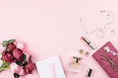 Fashion collection with accessories, flowers, cosmetics and jewelry on pink background, copyspace. Womens Day concept, top view