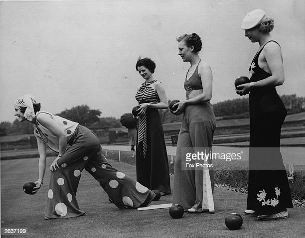 Fashion conscious girls in beach pyjamas playing bowls on a bowling green