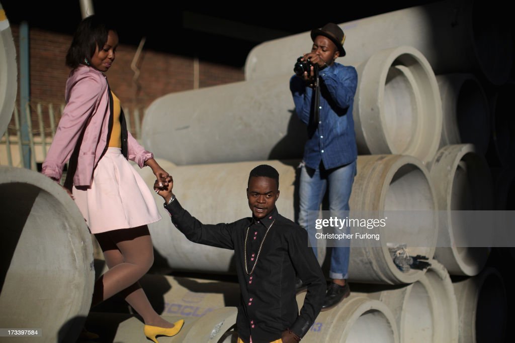 Fashion conscious youths pose for and take photographs of each other as daily life continues as former president Nelson Mandela remains in critical condition on July 13, 2013 in Johannesburg, South Africa. Former South African President Nelson Mandela has been hospitalized at the Medi-Clinic Hospital in Pretoria for five weeks his wife Graca Machel has said she was less anxious about his condition on July 12, five weeks after he was admitted to hospital.