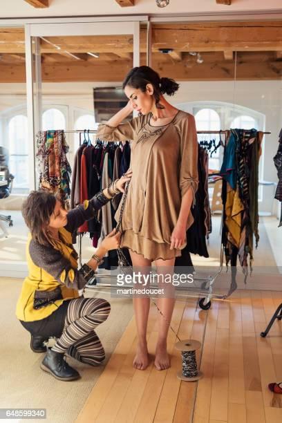 Fashion designer adjusting clothing on female model.