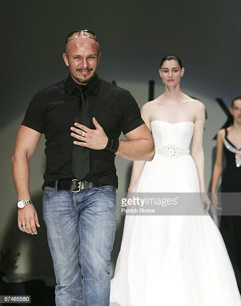 Fashion designer Alex Perry salutes the crowd at the end of the presentation of his collection in the Overseas Passenger Terminal during Mercedes...
