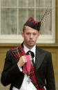 Fashion designer Alexander McQueen poses with the CBE that he received from Queen Elizabeth II during investitures 29 October 2003 at Buckingham...