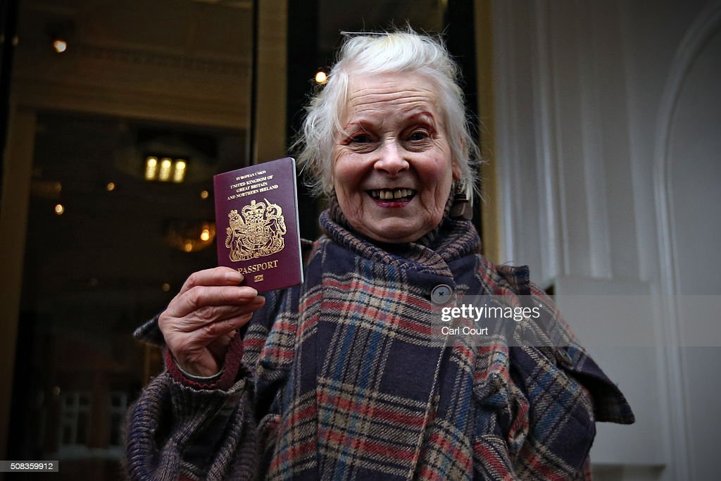 Fashion designer and political activist Vivienne Westwood holds up her passport as she arrives to visit Wikileaks founder Julian Assange as he...