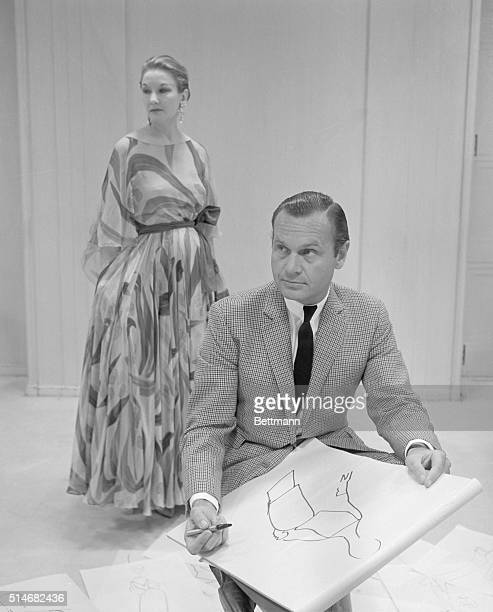 Fashion designer Bill Blass sketches a shape for a dress while a model in one of his creations stands nearby