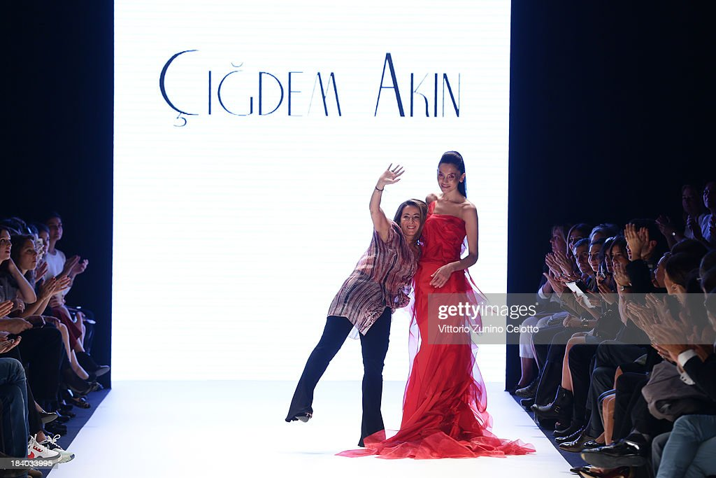 Fashion designer Cigdem Akin (L) and a model walk the runway at the Cigdem Akin show during Mercedes-Benz Fashion Week Istanbul s/s 2014 Presented By American Express on October 11, 2013 in Istanbul, Turkey.