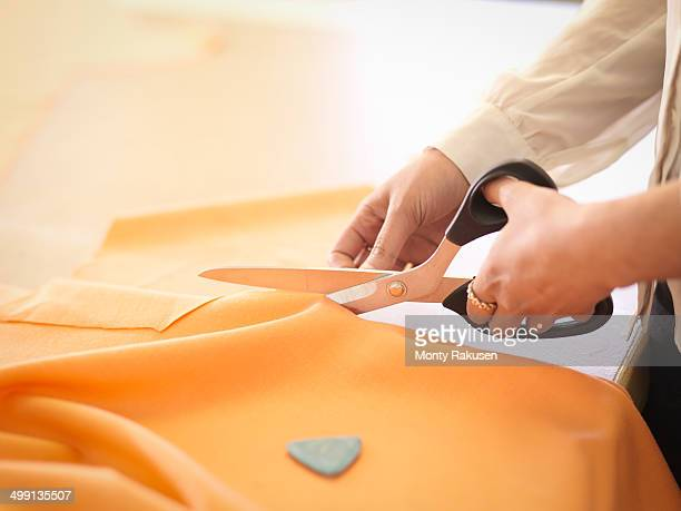 Fashion designer cutting cloth in fashion design studio, close up