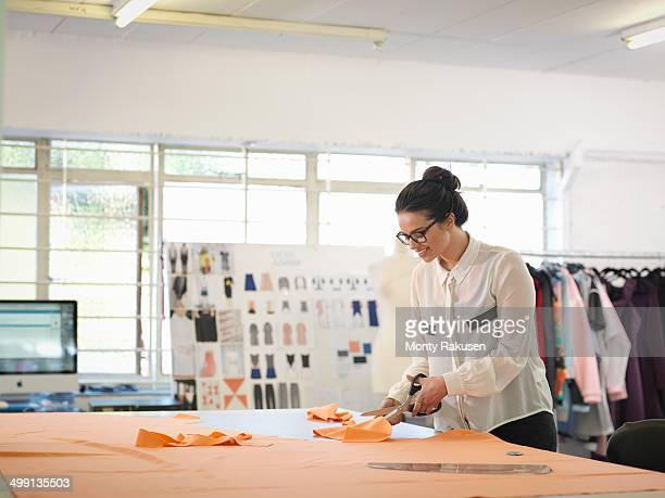 Fashion designer cutting cloth in fashion design studio
