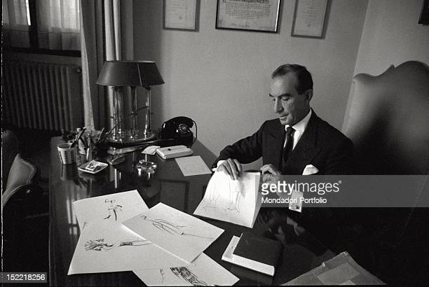 Fashion designer Emilio Pucci heir to an extremely ancient Florentine aristocratic family at his desk at work comparing and elaborating some sketches...