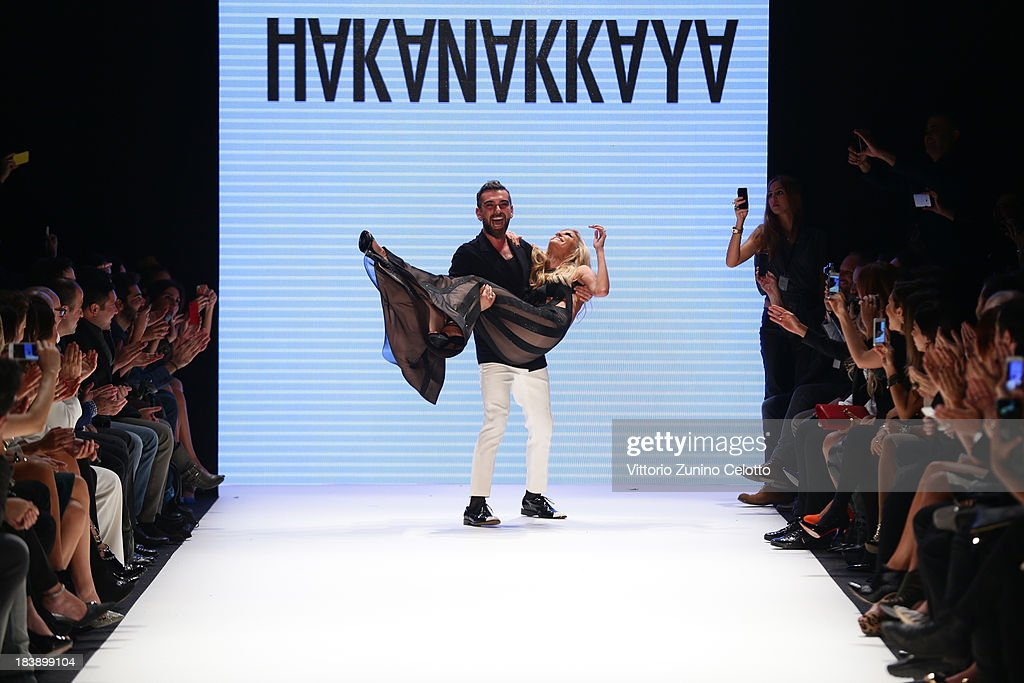 Fashion designer Hakan Akkaya (L) and model Cagla Sikel (R) walk the runway at the Hakan Akkaya show during Mercedes-Benz Fashion Week Istanbul s/s 2014 presented by American Express on October 9, 2013 in Istanbul, Turkey.