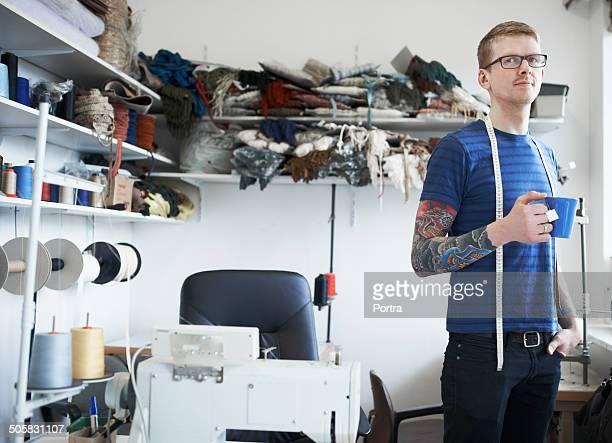 Fashion designer having coffee in workshop