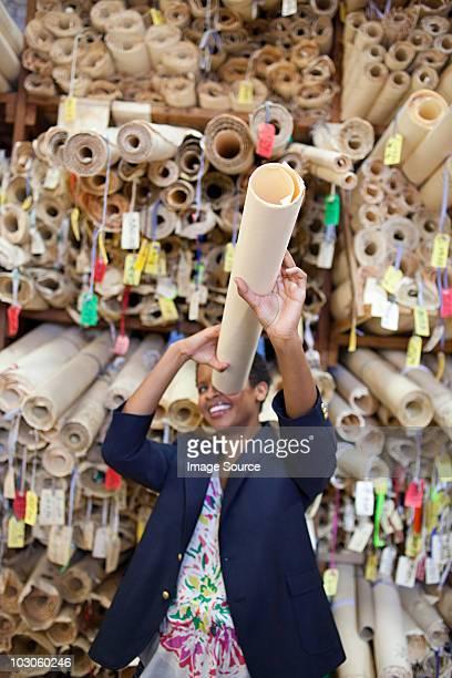 Fashion designer holding rolled up pattern to eye