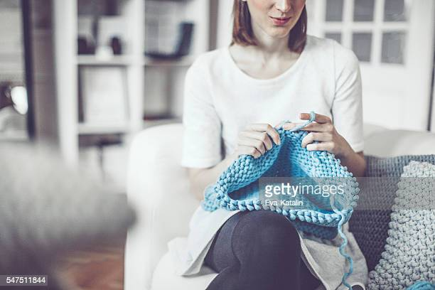 Fashion designer is knitting in her showroom