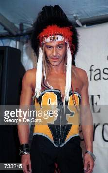 Fashion designer John Galliano poses for photographers backstage at the VH1 2000 Fashion Awards October 20 2000 in New York City