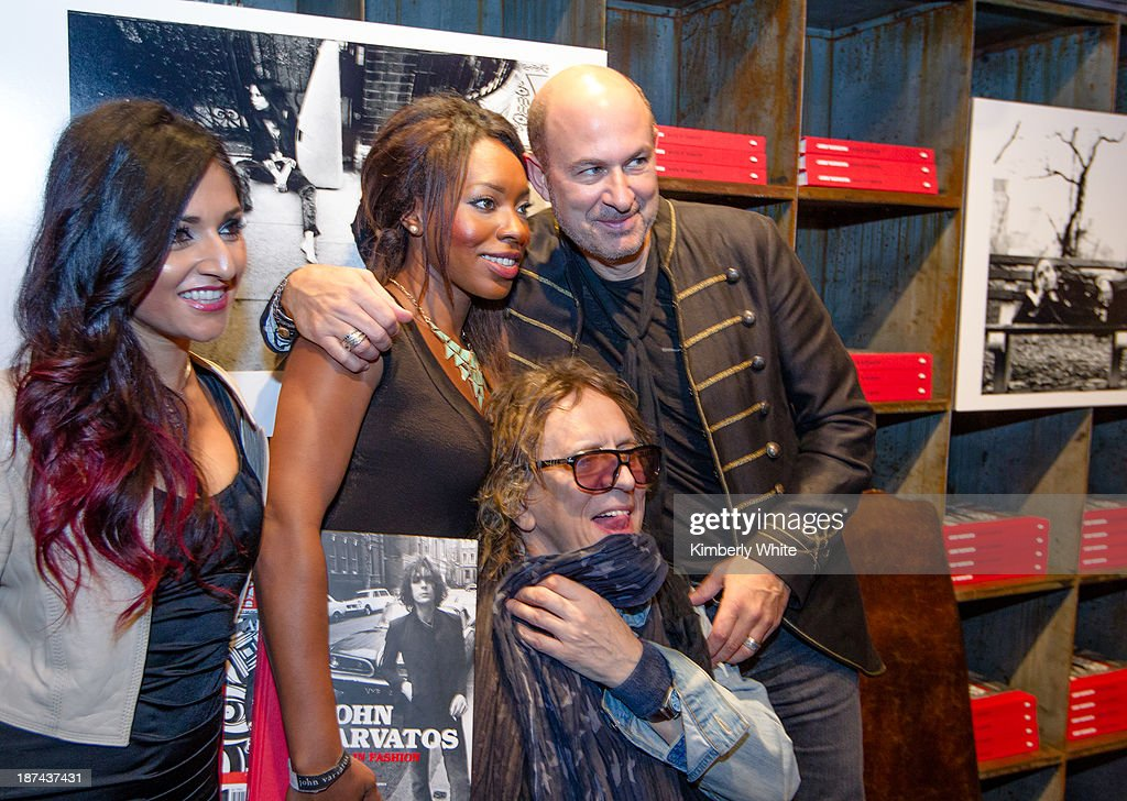 Fashion designer John Varvatos (R) and photographer Mick Rock embrace fans at the launch of the book 'Rock In Fashion' at John Varvatos on November 8, 2013 in San Francisco, California.