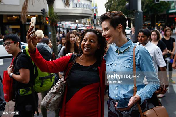 Fashion designer Karen Walker poses with shoppers waiting in line for the opening of New Zealand's first TopShop and TopMan store on Queen Street on...