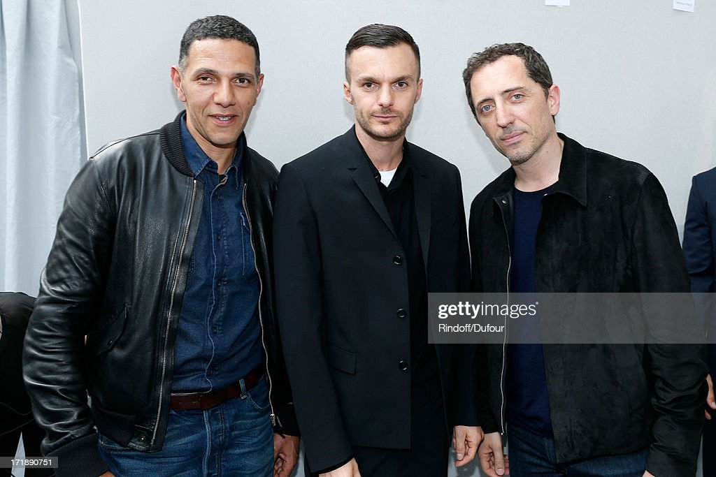 Fashion designer Kris Van Assche standing between actor <a gi-track='captionPersonalityLinkClicked' href=/galleries/search?phrase=Roschdy+Zem&family=editorial&specificpeople=606839 ng-click='$event.stopPropagation()'>Roschdy Zem</a> (L) and humorist <a gi-track='captionPersonalityLinkClicked' href=/galleries/search?phrase=Gad+Elmaleh&family=editorial&specificpeople=586672 ng-click='$event.stopPropagation()'>Gad Elmaleh</a> backstage after Dior Homme Menswear Spring/Summer 2014 Show as part of the Paris Fashion Week on June 29, 2013 in Paris, France.