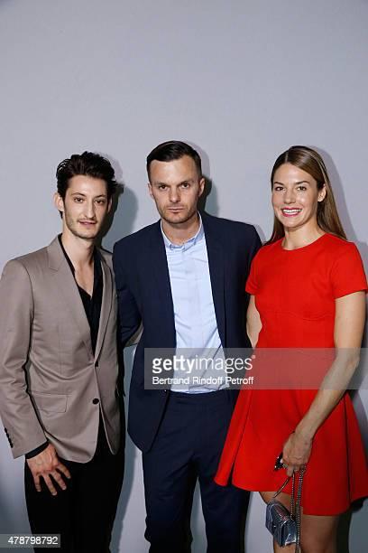 Fashion designer Kris Van Assche standing between Actors Natasha Andrews and Pierre Niney pose Backstage after the Dior Homme Menswear Spring/Summer...