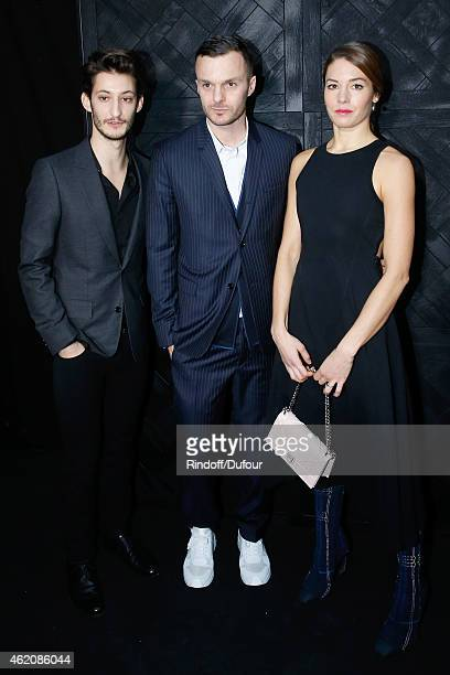 Fashion designer Kris Van Assche standing between Actors Pierre Niney and his Companion Natasha Andrews pose backstage after the Dior Homme Menswear...