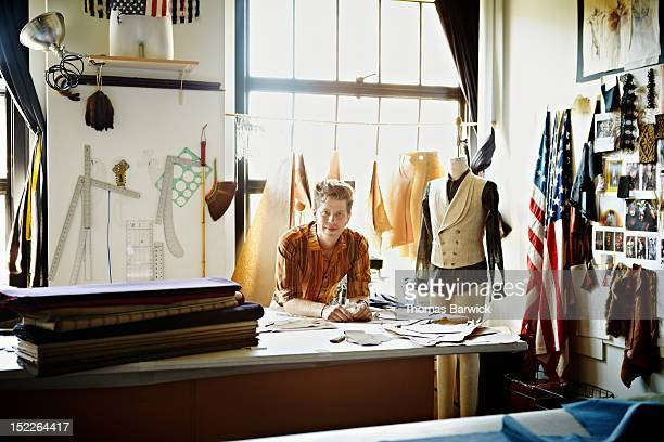 Fashion designer leaning on workbench in studio