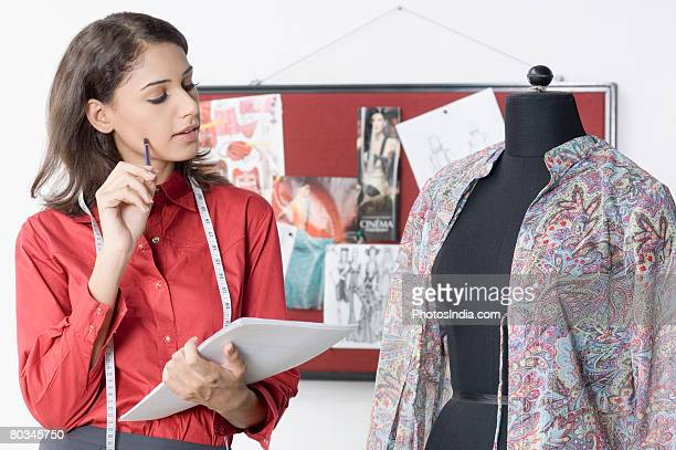 Fashion designer looking a mannequin and holding documents