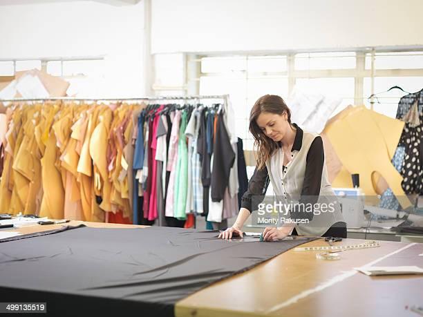 Fashion designer measuring fabric in fashion design studio