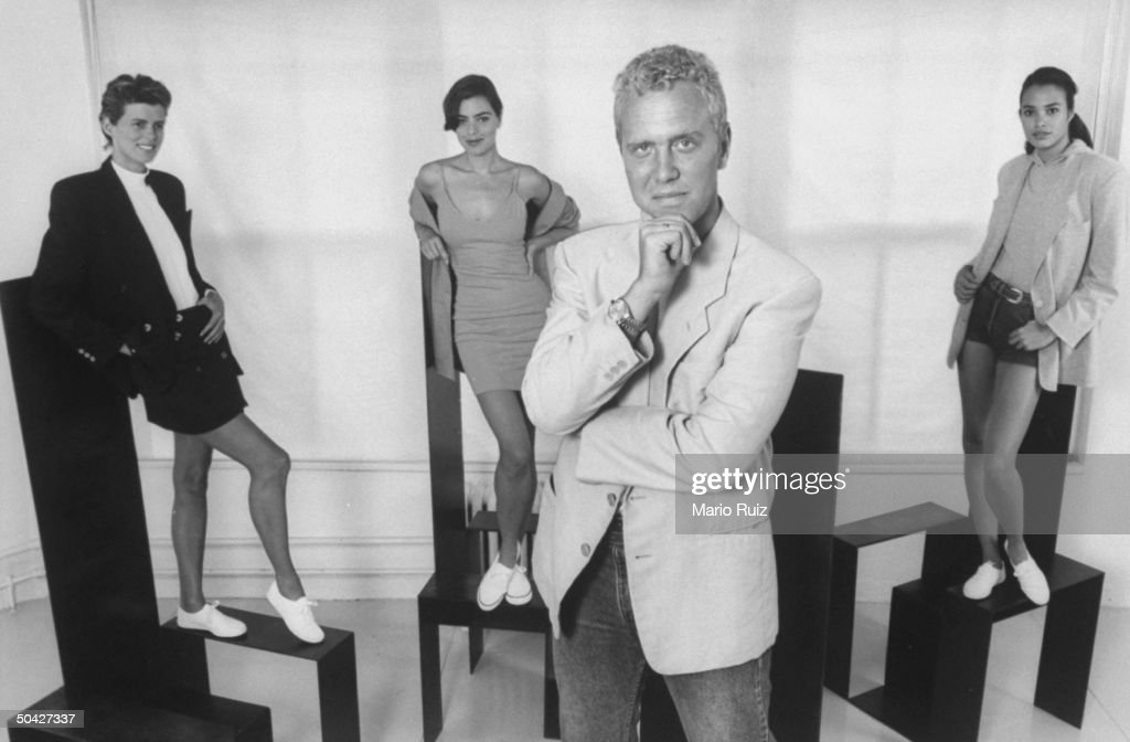 Fashion designer Michael Kors posing in front of three female models on pedestals, showing off his sports fashions incl. short skirt & jacket ensemble; one-piece knit, tank top dress & short shorts w. jacket in his showroom.