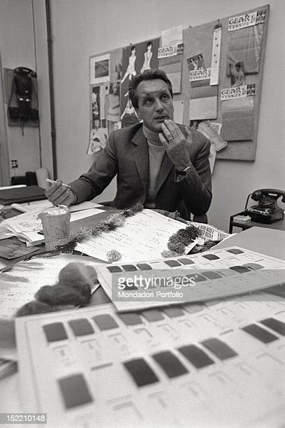 Fashion designer Ottavio Missoni sitting at his desk in his study full of sketches and sheets Italy 1968