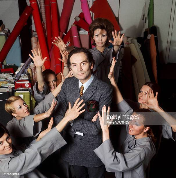 Fashion designer Pierre Cardin stands in his studio surrounded by models