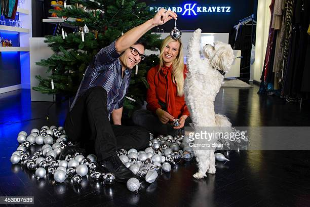Fashion designer Richard Kravetz his dog Coco and TV host Nadine Krueger pose during a photo session in front of a christmas tree on December 01 2013...