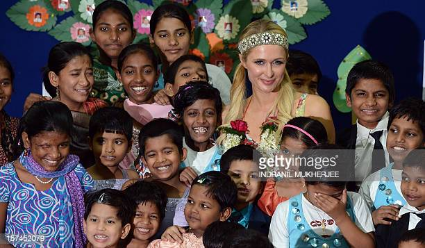 Fashion designer socialite and DJ Paris Whitney Hilton poses with children during a visit to an orphanage in Mumbai on December 3 2012 The American...