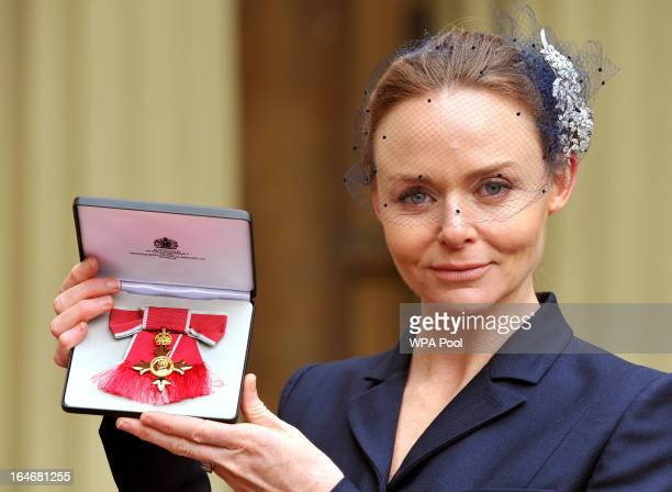 Fashion designer Stella McCartney holds her Officer of the British Empire award after the Investiture Ceremon at Buckingham Palace on March 26 2013...