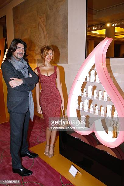 Fashion Designer Stephane Rolland and Zahia Dehar poses in front of Zahia's Christmas Tree during the 19th Edition of 'Les Sapins de Noel des...