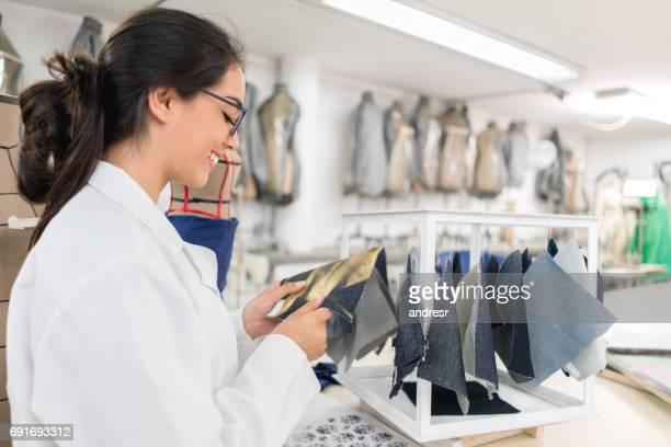 Fashion designer student looking at fabrics