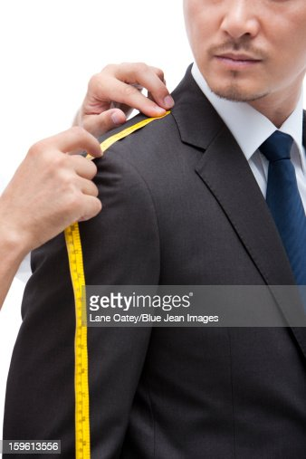 Fashion designer taking a measurement of  businessman